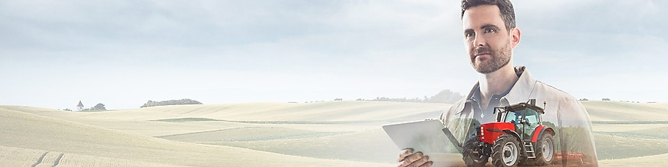 man reading a document with a background of fields and a red tractor